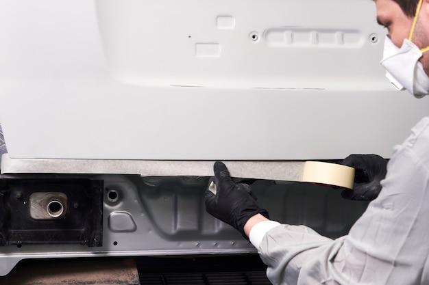 Monteur die auto bedekt met eendband alvorens in de autoreparatiedienst te schilderen
