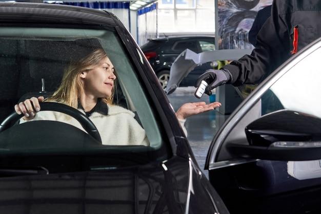 Monteur die autosleutels geeft aan vrouwelijke klant na het onderhoud
