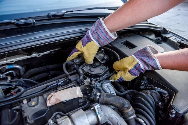 Monteur die de motor van een auto onder de motorkap van dichtbij onderzoekt