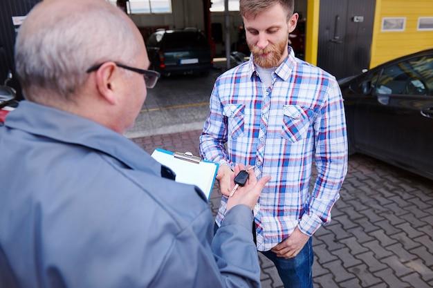 Monteur die de sleutelsauto aan een klant geeft