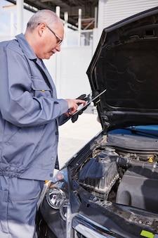 Monteur die een auto controleert