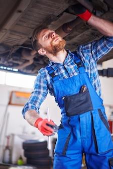 Monteur die een auto in de werkplaats herstelt
