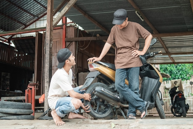 Monteur die een klant helpt om scootermotor te repareren