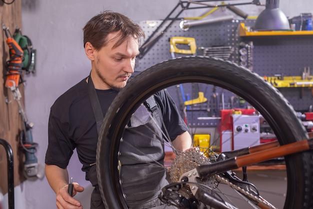 Monteur die een mountainbike in een werkplaats herstelt