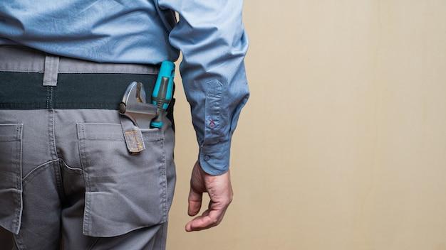 Monteur draagt een grijs uniform met reparatiegereedschap op de zakken
