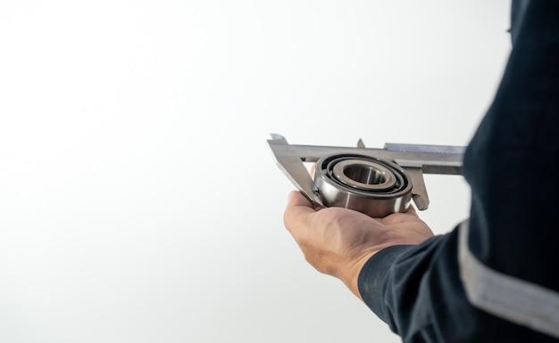 Monteur gebruikt schuifmaat voor het meten van de grootte van het lager