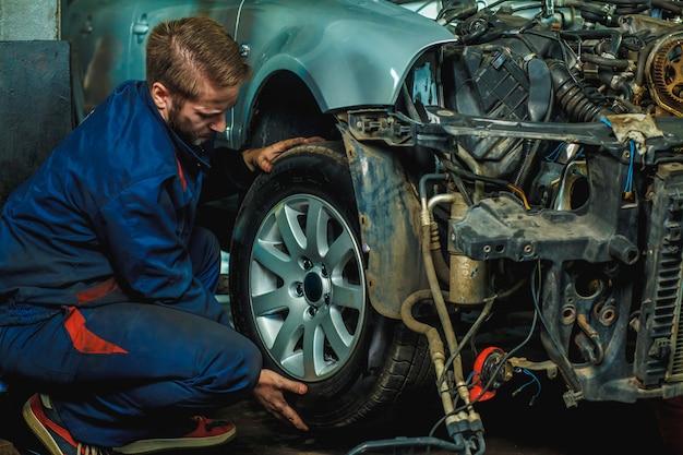 Monteur gerepareerde voertuigen op wielen. mechanic holding car tyre bij garage.