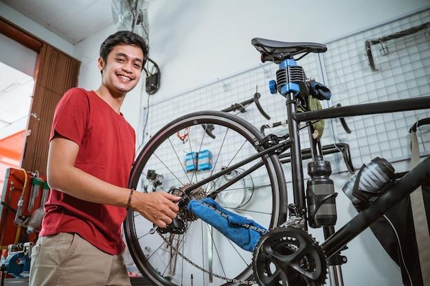 Monteur glimlach tijdens het werk draai de fietsas vast met een sleutel