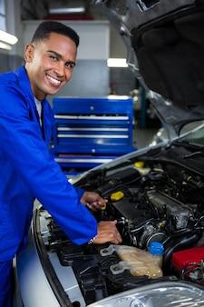 Monteur het controleren van het oliepeil in een automotor