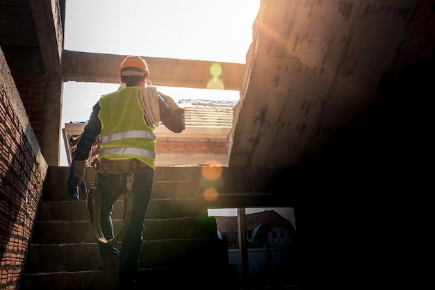 Monteur houd het witte koord vast met persoonlijke beschermingsmiddelen. toezicht houden op de bouw van het huis bouwtoezichthouders zien interieurklussen woningbouw