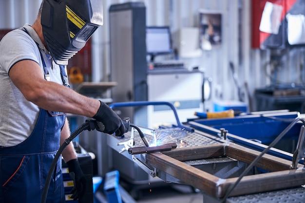 Monteur in beschermende helm die metalen auto-onderdelen in garage lassen