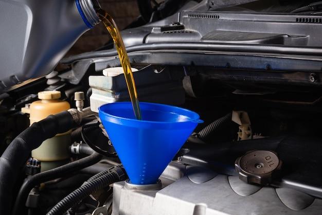 Monteur in dienst om de auto te repareren, bij te tanken en uit de fles te gieten om smeerolie te verversen