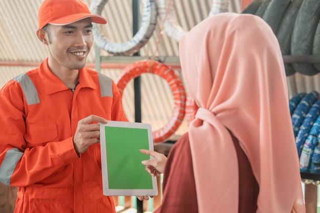 Monteur in een wearpack die een digitale tablet draagt met een klant in een bandenrek