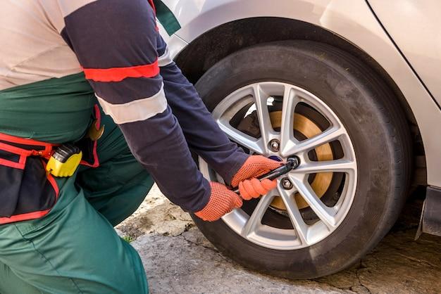 Monteur in gewaad die autowiel bevestigt. autoserviceconcept met monteur die auto repareert