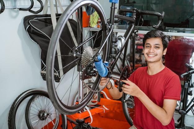 Monteur in rode kleren die zorgvuldig een fietscrankstel assembleert