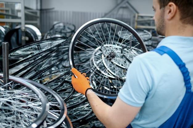 Monteur in uniform houdt fietswiel op fabriek. montage van fietsvelgen en spaken in de werkplaats, montage van fietsonderdelen