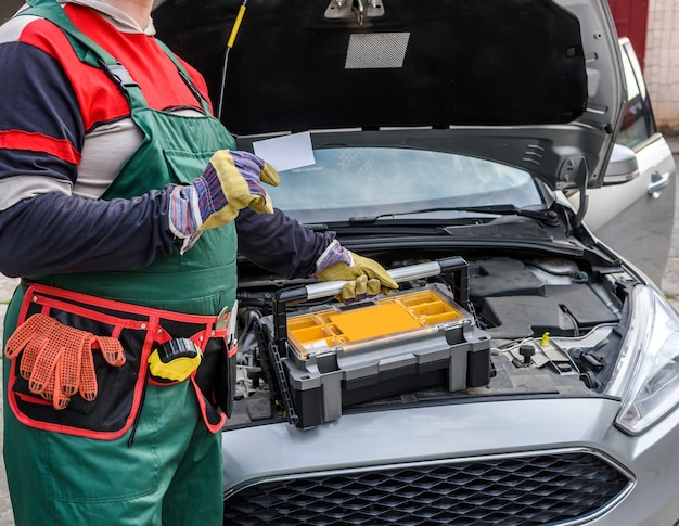 Monteur in uniform poseren met gereedschapskist in de buurt van motor van een auto