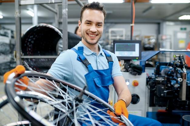 Monteur in uniform werkt met fietswiel op fabriek. montage van fietsvelgen en spaken in de werkplaats, montage van fietsonderdelen