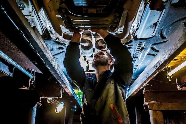 Monteur in uniform werkzaam in autoservice met opgeheven voertuig