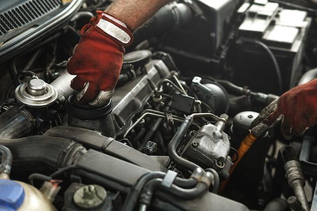 Monteur inspecteert kapotte auto in de autoreparatiewerkplaats