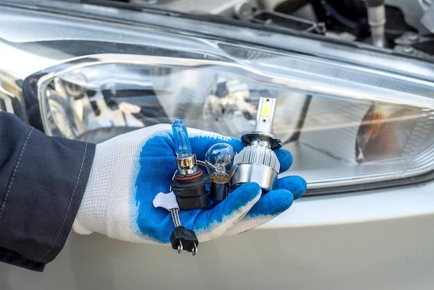 Monteur installeren veranderende moderne halogeen koplamp lamp. lichttechniek.