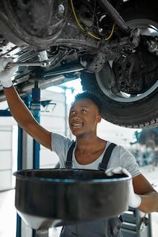 Monteur man aftapt de olie in mechanische werkplaats