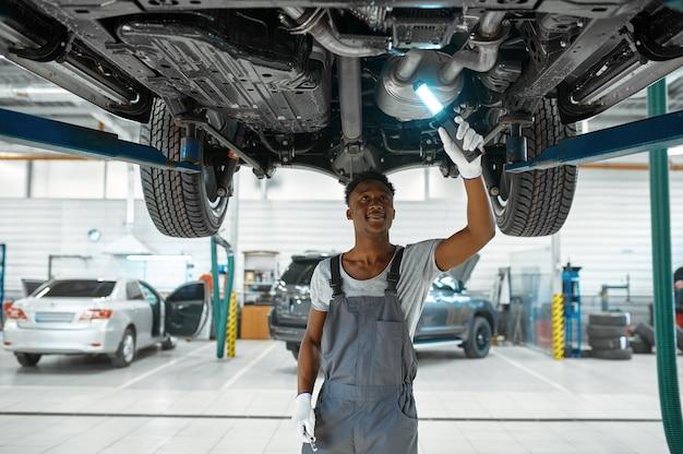 Monteur man controleert auto-ophanging in mechanische werkplaats