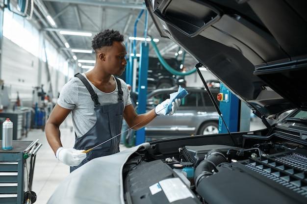 Monteur man controleert oliepeil in mechanische werkplaats