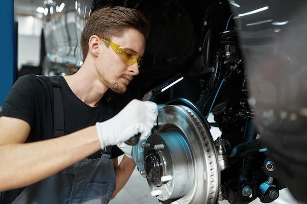 Monteur man controleert remschijf in mechanische werkplaats