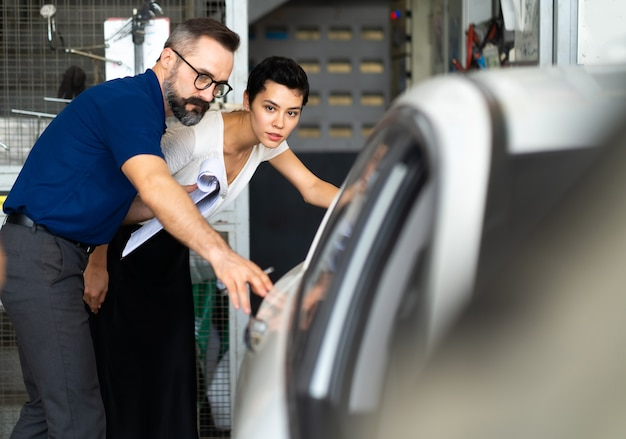 Monteur man en vrouw klant controleren de staat van de auto voor levering. garage voor auto reparatie onderhoudsstation.