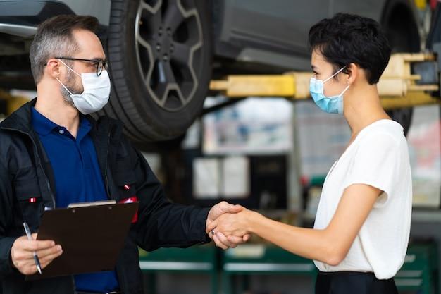 Monteur man en vrouw klant die medische gezichtsmasker bescherming coronavirus draagt en de staat van de auto vóór levering controleren.