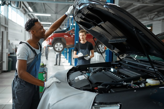 Monteur man inspecteert motor in mechanische werkplaats.