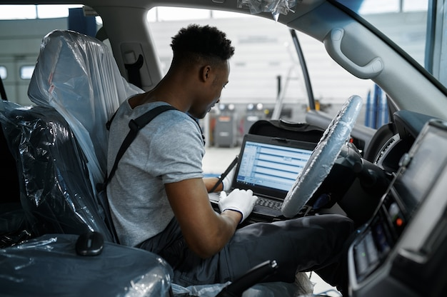 Monteur man met laptop bij de auto met geopende kap in mechanische werkplaats