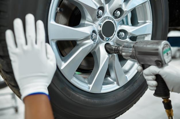Monteur man met pneumatisch pistool bevestigt wiel in mechanische werkplaats