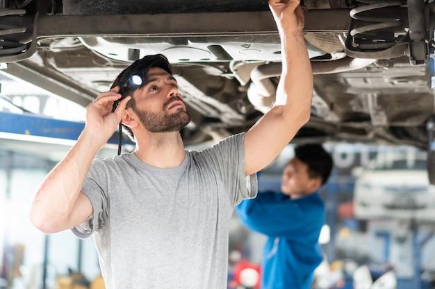 Monteur man met zaklamp controleren onder auto en repareren bij auto reparatiewerkplaats
