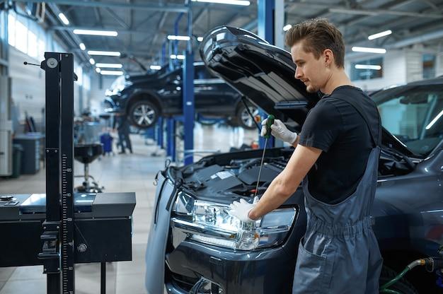 Monteur man past de koplampen in mechanische werkplaats aan