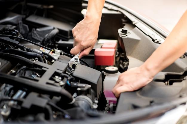 Monteur man werken en reparatie motor van een auto in het centrum van de auto service. van moderne voertuigmotor, industrie, mechanic en business.