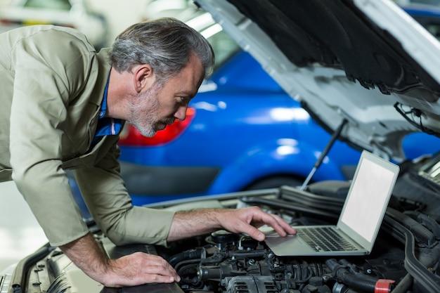 Monteur met behulp van laptop, terwijl het onderhoud van motor van een auto