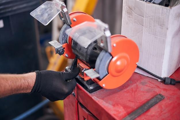 Monteur met behulp van slijpmachine bij auto reparatiewerkplaats