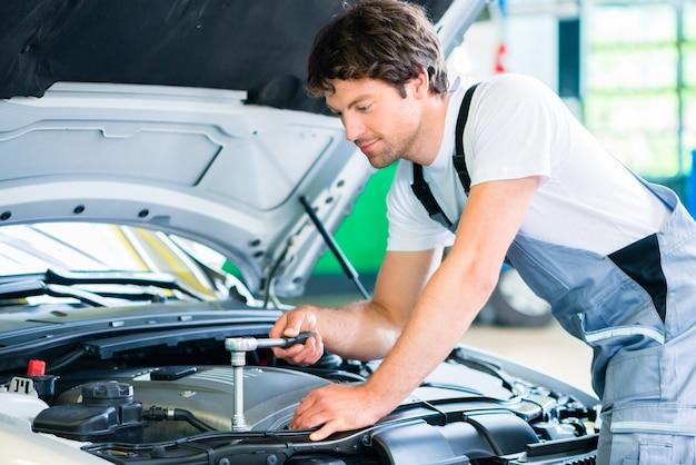 Monteur met diagnostisch hulpmiddel in autowerkplaats