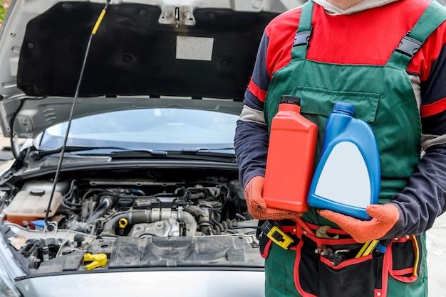 Monteur met flessen met olie in de buurt van motor van een auto