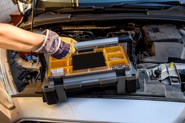 Monteur met gereedschapskist in de buurt van kapotte auto