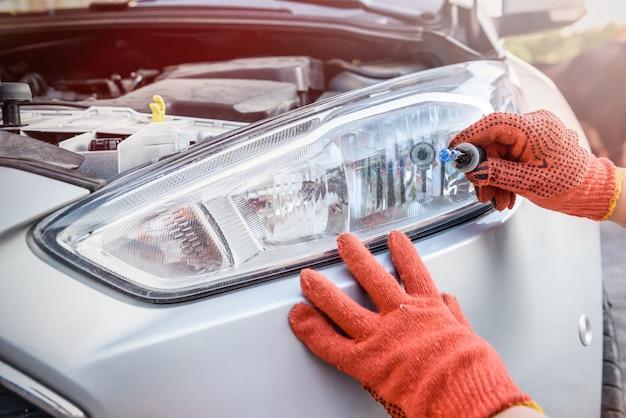 Monteur met lamp en kabels van koplamp van auto