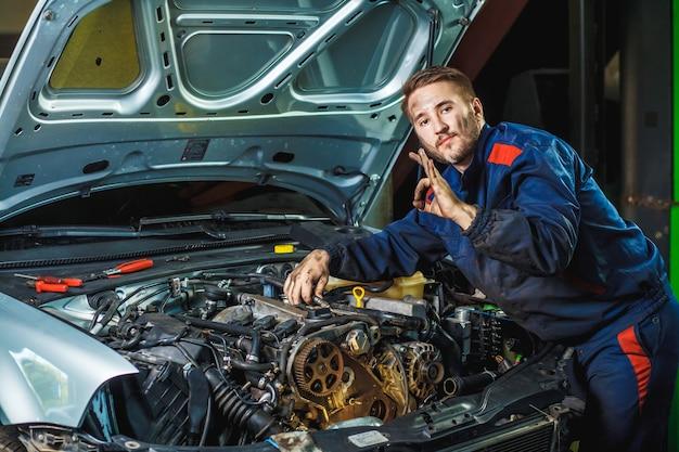 Monteur met moersleutelreparatiemotor van een auto
