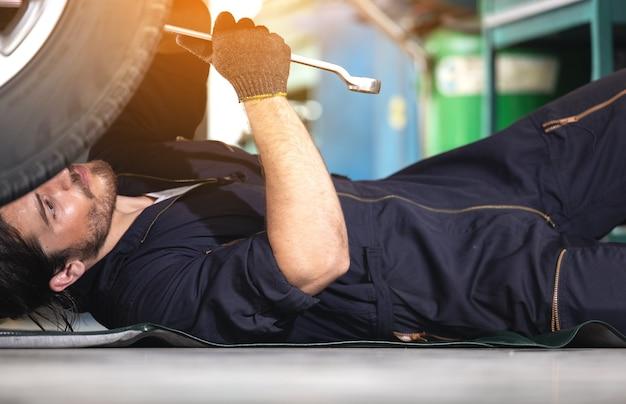 Monteur onderhoud autoband met slagpistool in garage van reparatie servicestation