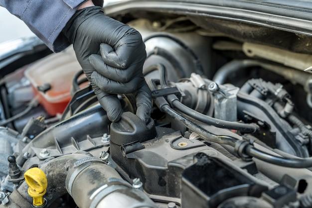 Monteur opent de oliedop om de olie van een automotor te verversen. auto service