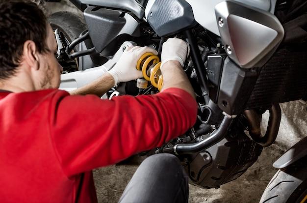 Monteur reparateur doet onderhoud of reparatie, reparatie op de motorfiets, motor, servicecentrum