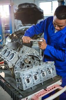 Monteur repareren onderdeel van de motor met een ratel