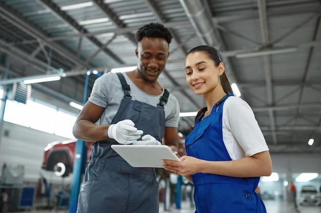 Monteur vrouw en man inspecteren motor in mechanische werkplaats.