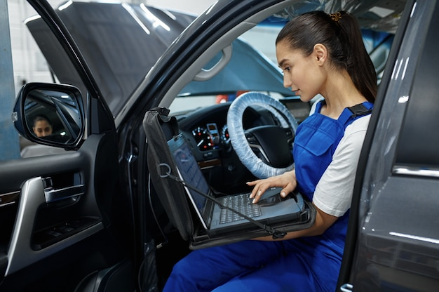 Monteur vrouw met laptop doet de motordiagnostiek in mechanische werkplaats, professionele inspectie